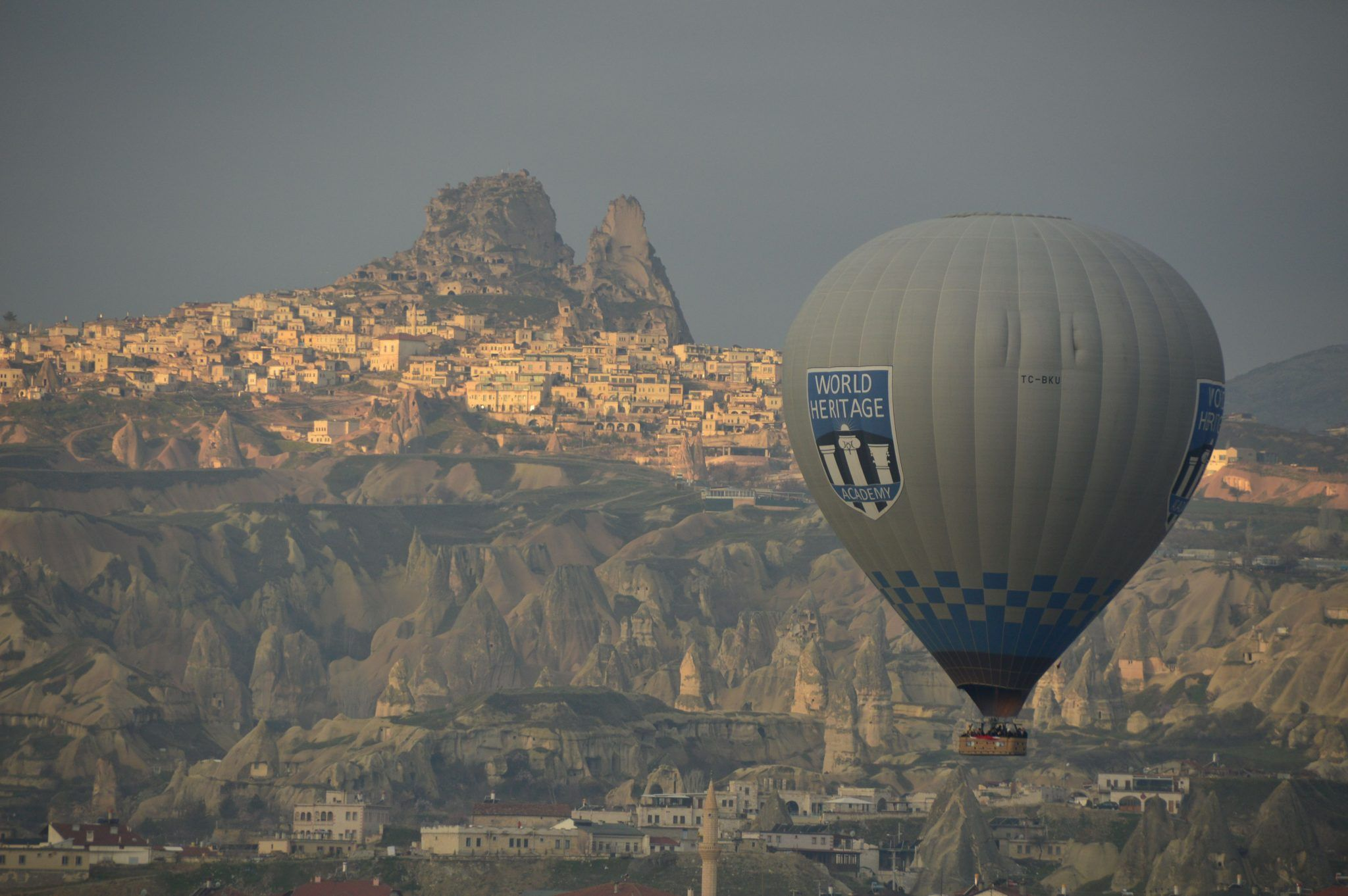 Hot air balloon with uchisar town behind it in Cappadocia turkey