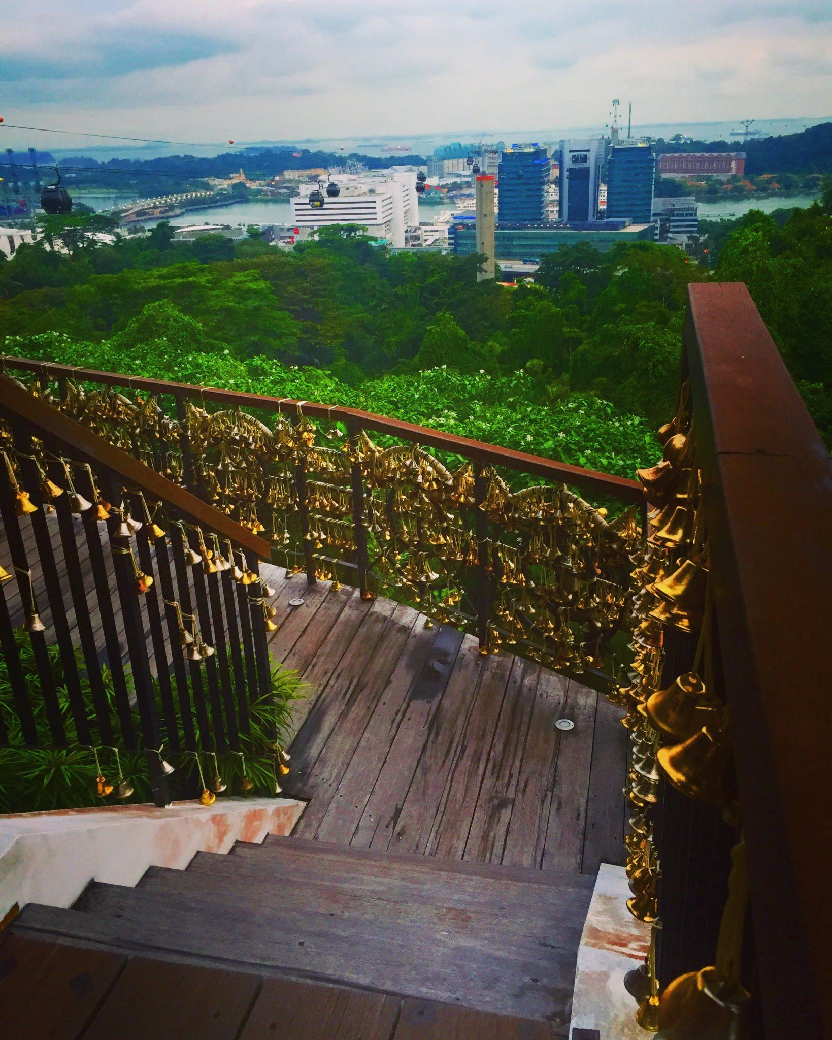 wooden stairs surrounded by bells at mount faber with a view of singapore