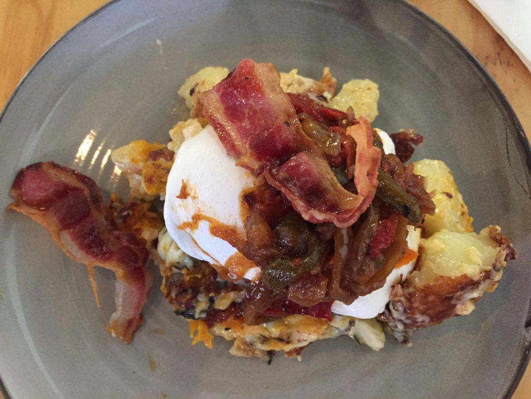 breakfast with poached eggs and bacon on a blue plate at Dee's dormana mornington peninsula victoria