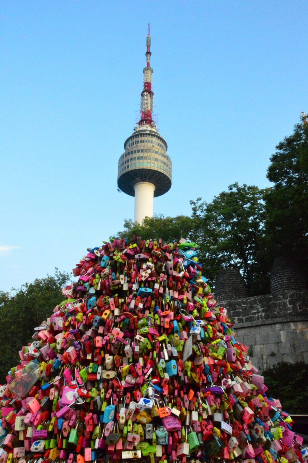 seoul tower with a stack of locks underneath it