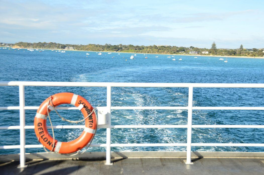 side of the queenscliff ferry with orange life saving tube and water behind