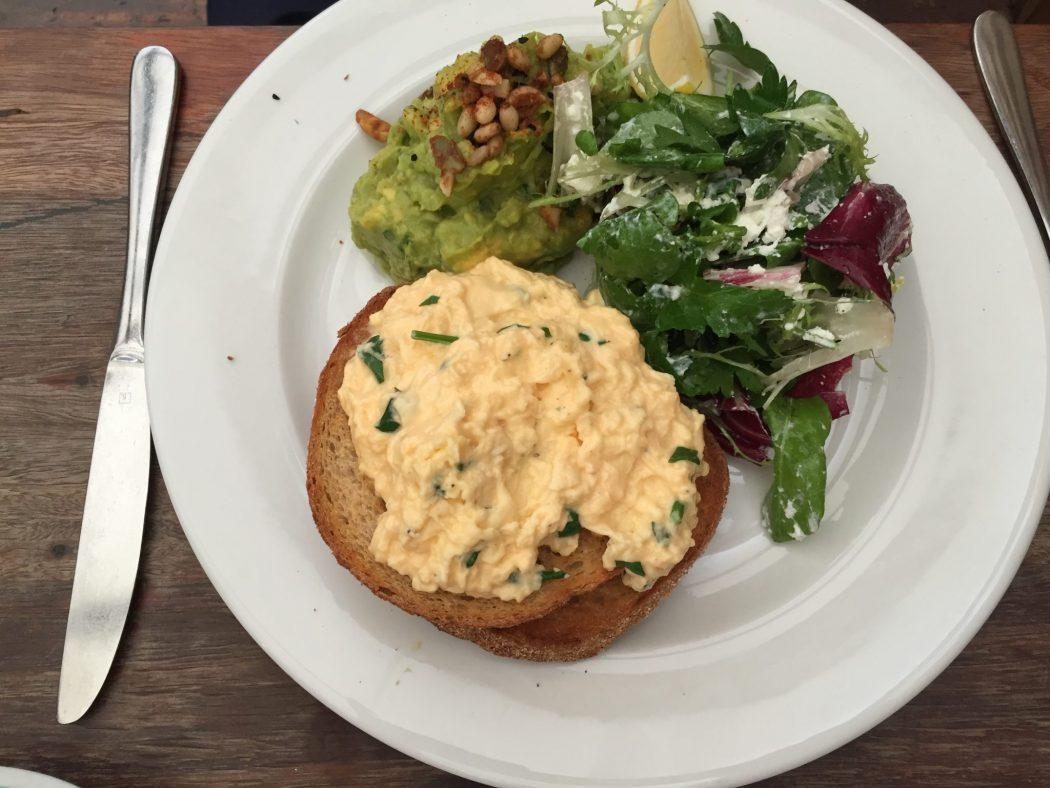 scrambled eggs with chives on toast and avocado and salad