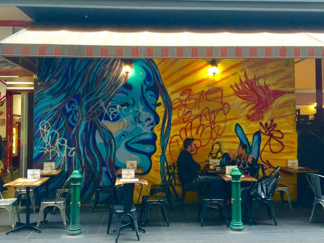 street art in front of cafe tables in melbourne