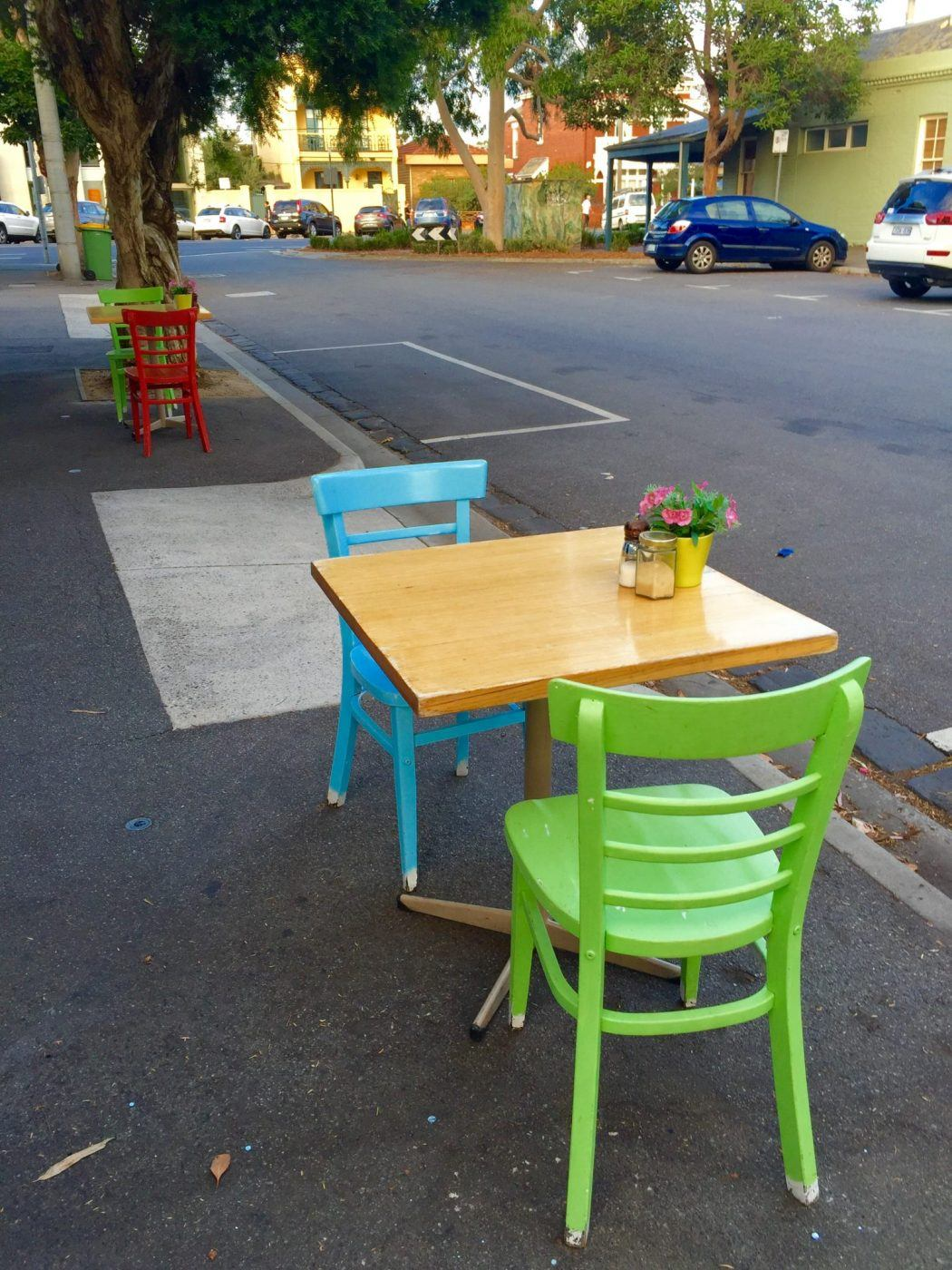 colourful chairs with wooden tables on the street at My Sista Says Port Melbourne