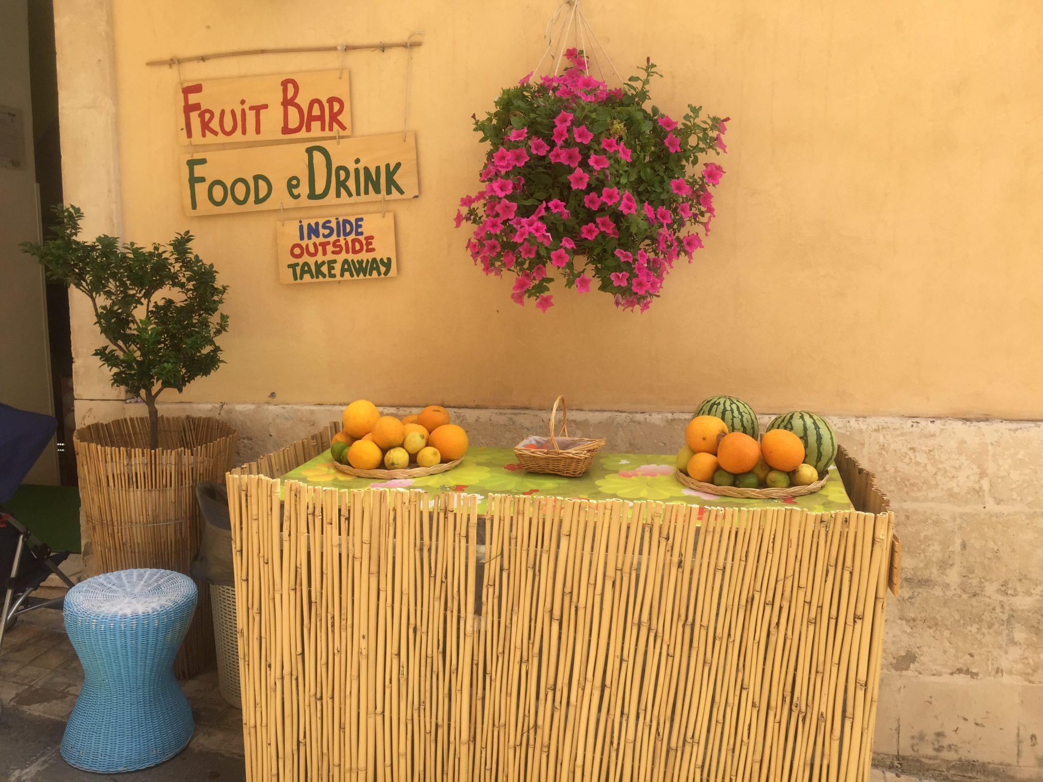 rustic signs above a table with fruit and a hanging basket noto sicily