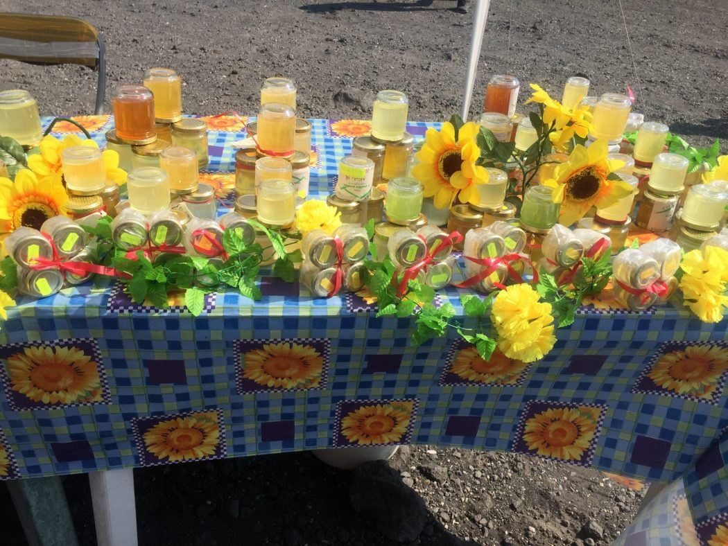 colourful table with honey for sale and sunflowers