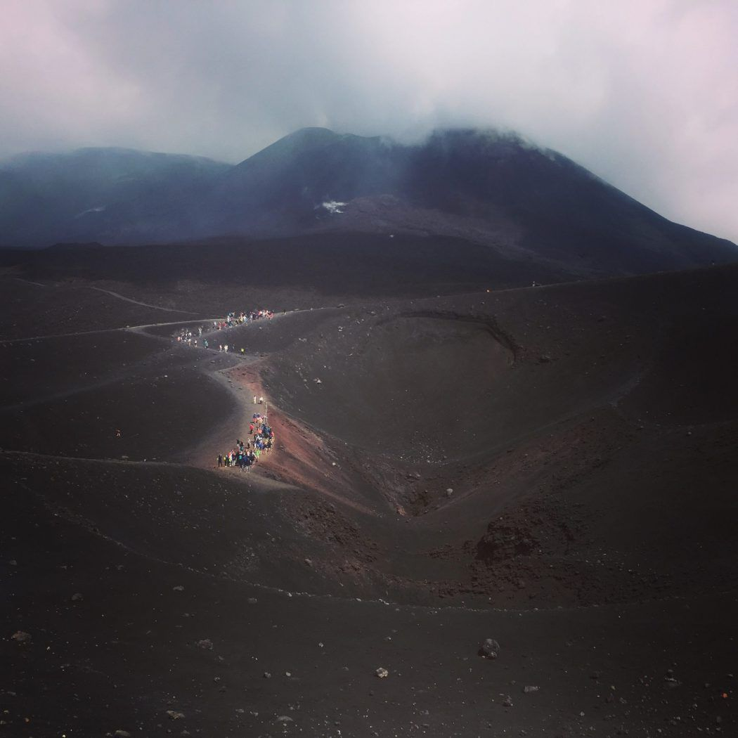 people in the distance climbing up a dark mount etna sicily