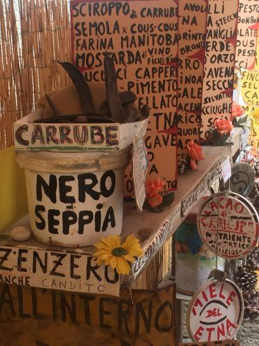 boxes and signs in italian at a market in syracuse sicily