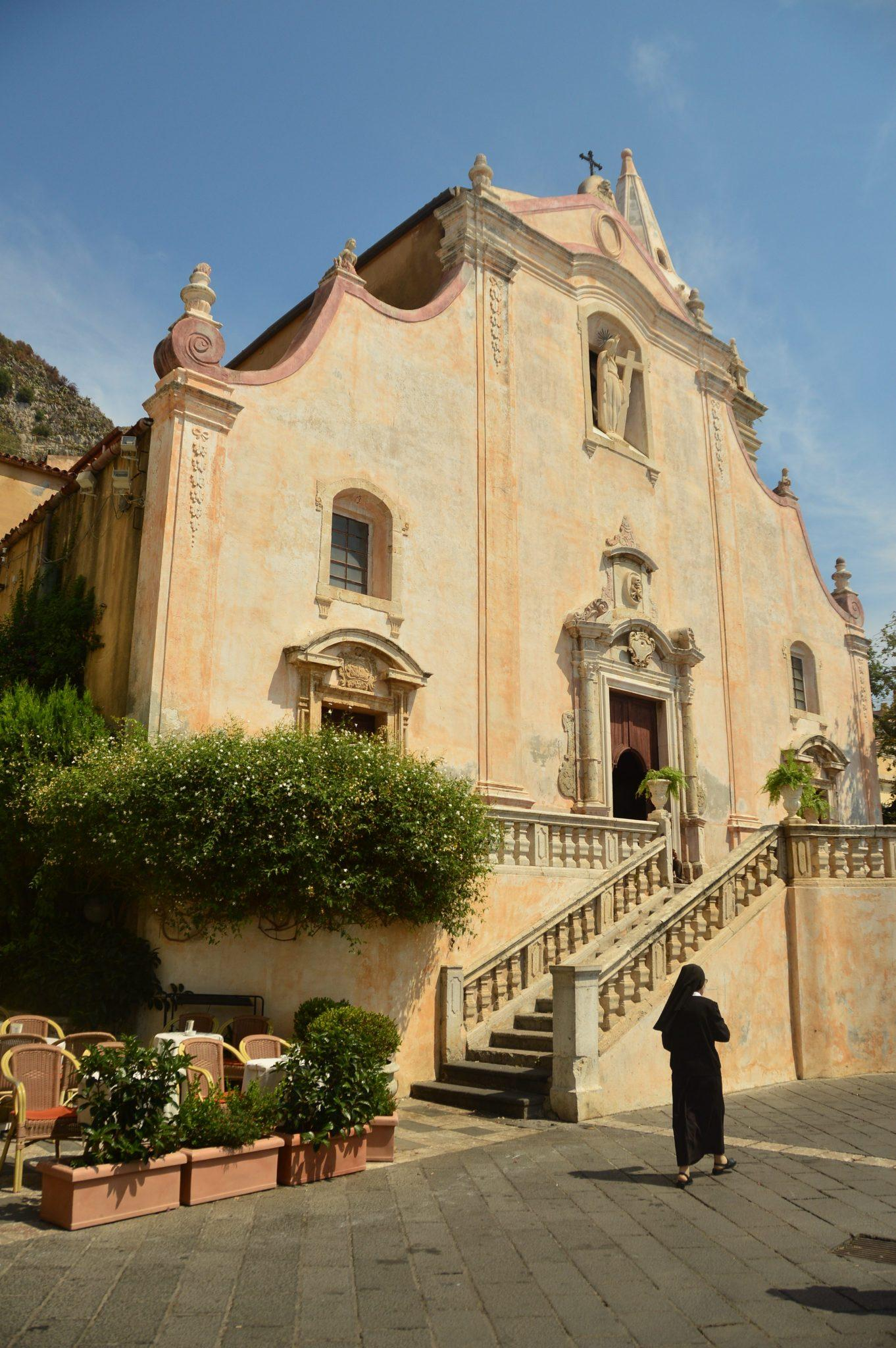 nun walks by a church in taormina sicily
