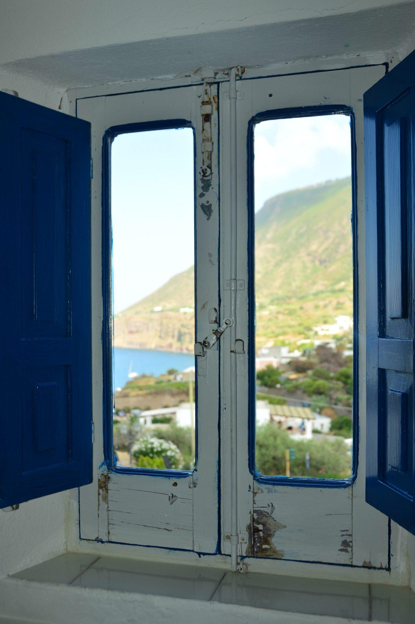 window with blue shutters looking onto an aeolian island