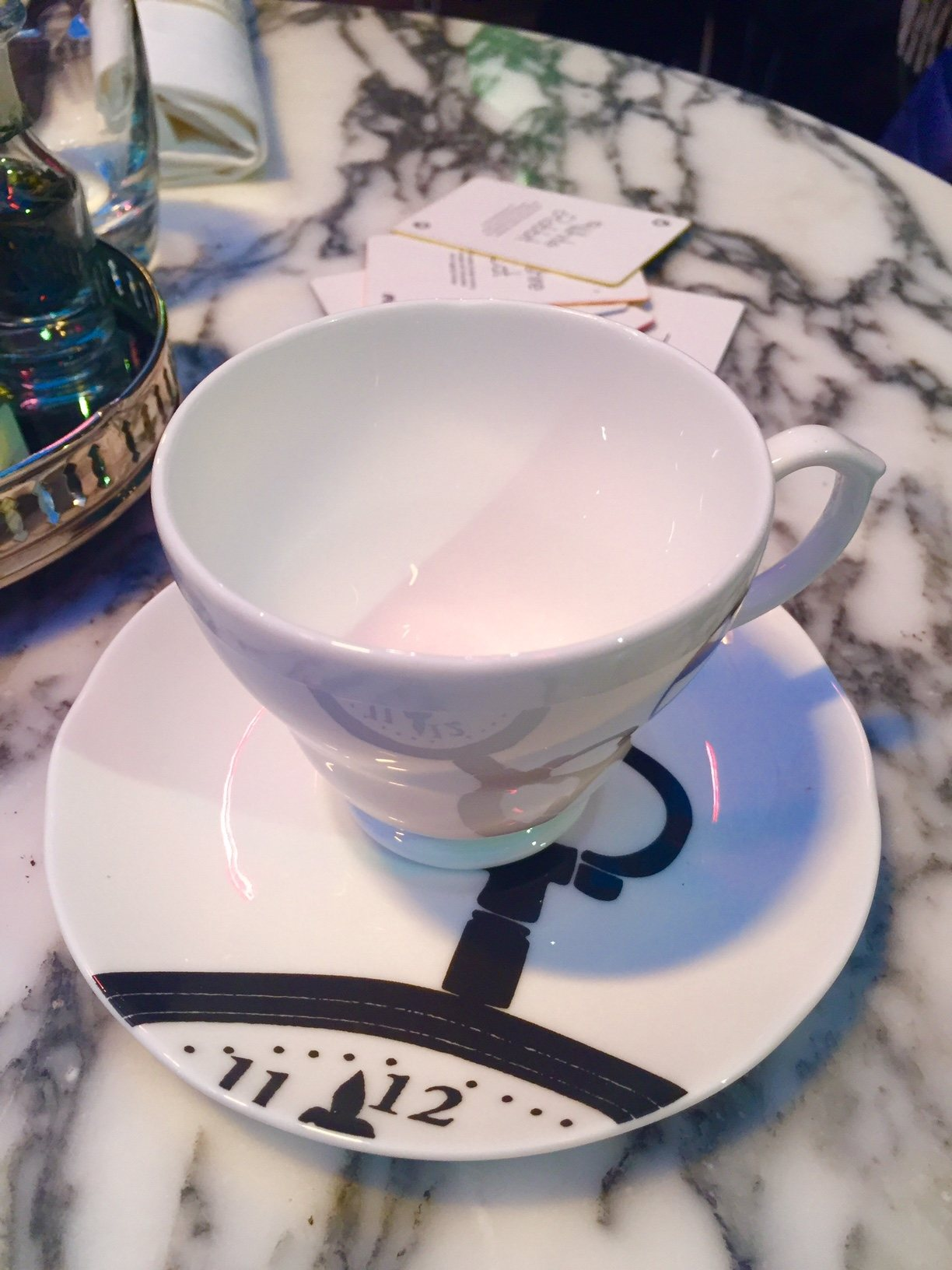 white cup and saucer with time graphic