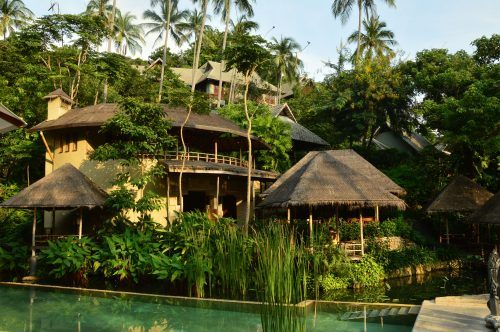 asian style multi layer buildings with palm trees and a pool in front kamalaya koh samui