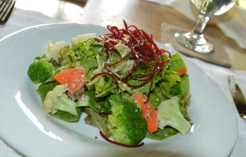 white plate with broccoli and greens and carrots on a table during the day