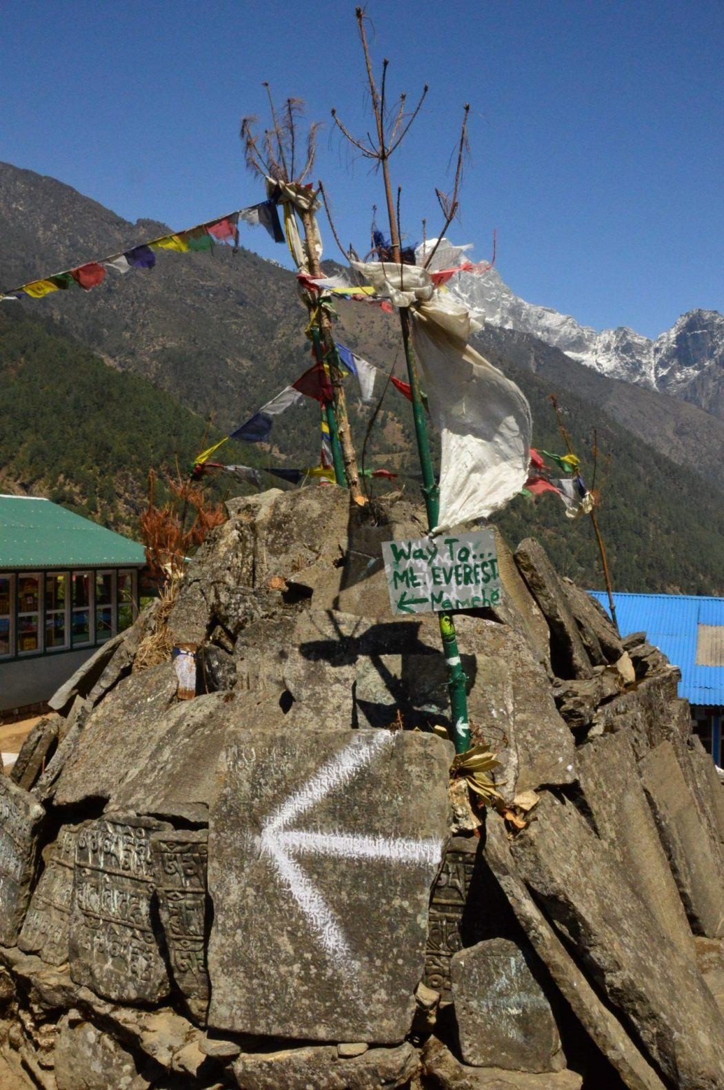 sign saying way to mt everest on a stack with prayer flags nepal