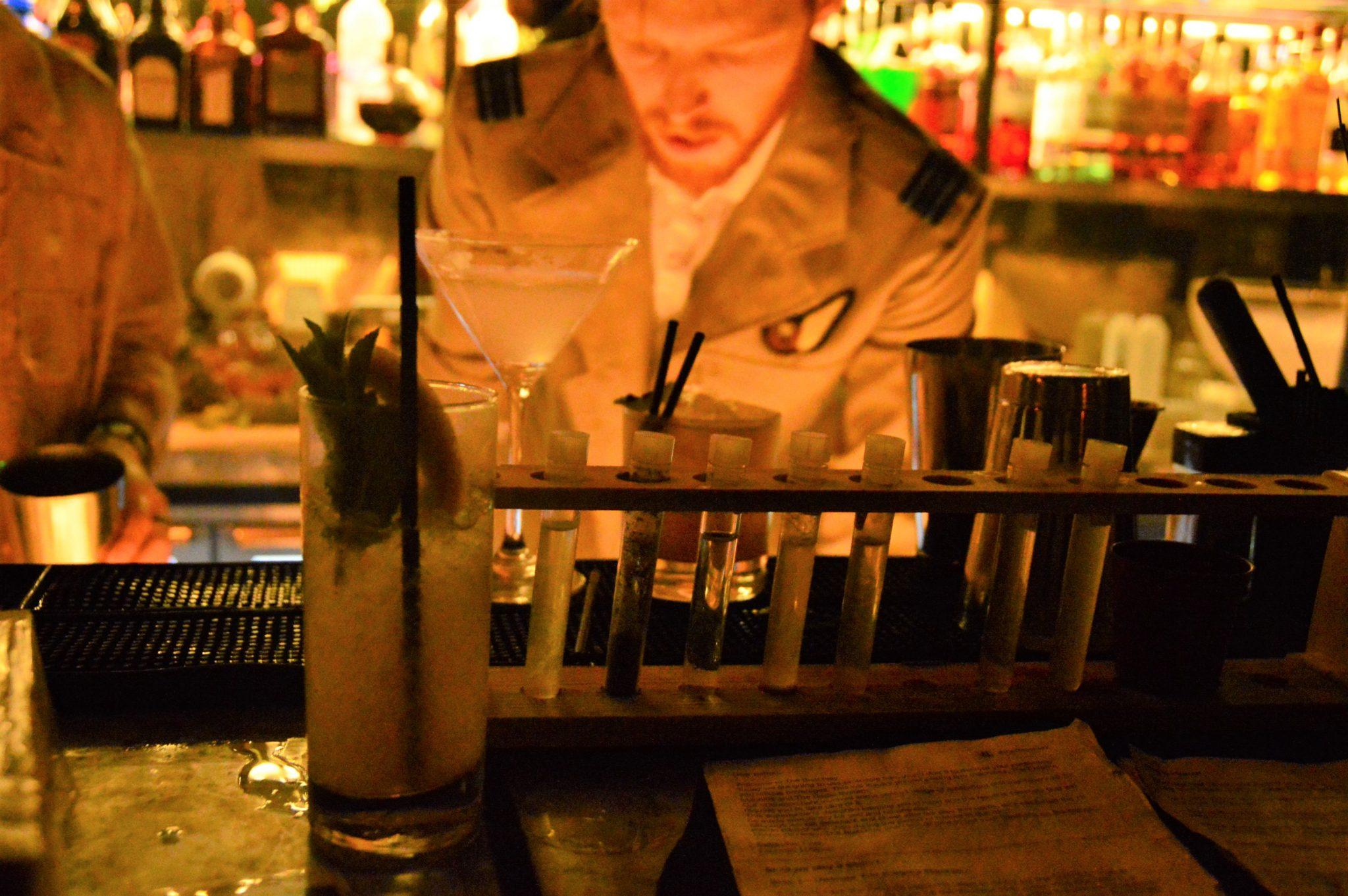 drinks in test tubes lined up at a bar
