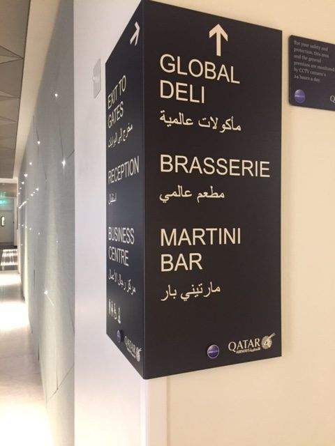 signs for different areas in the qatar business class lounge at heathrow