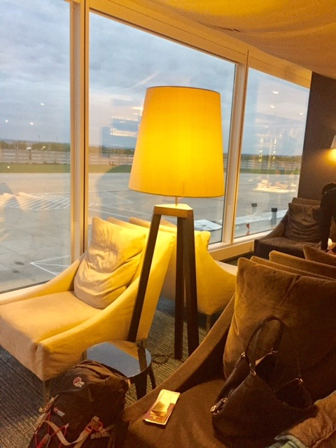 chair with lamp against a window in the qatar business class lounge at heathrow airport