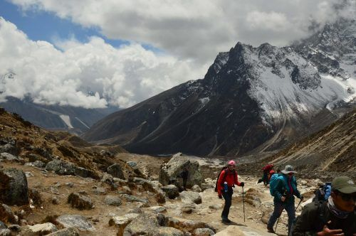 trekkers with mountains and clouds behind them in nepal