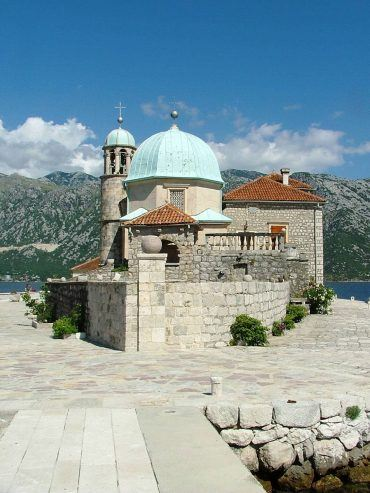 the small church and stone buildings on our lady of the rocks island montenegro