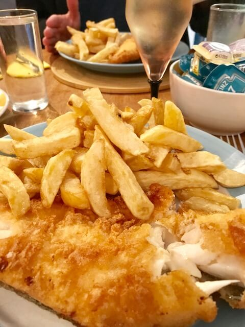 plate with fish and chips and glass of wine