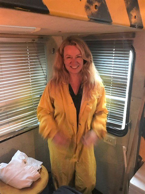 woman in yellow boiler suit inside winnebago