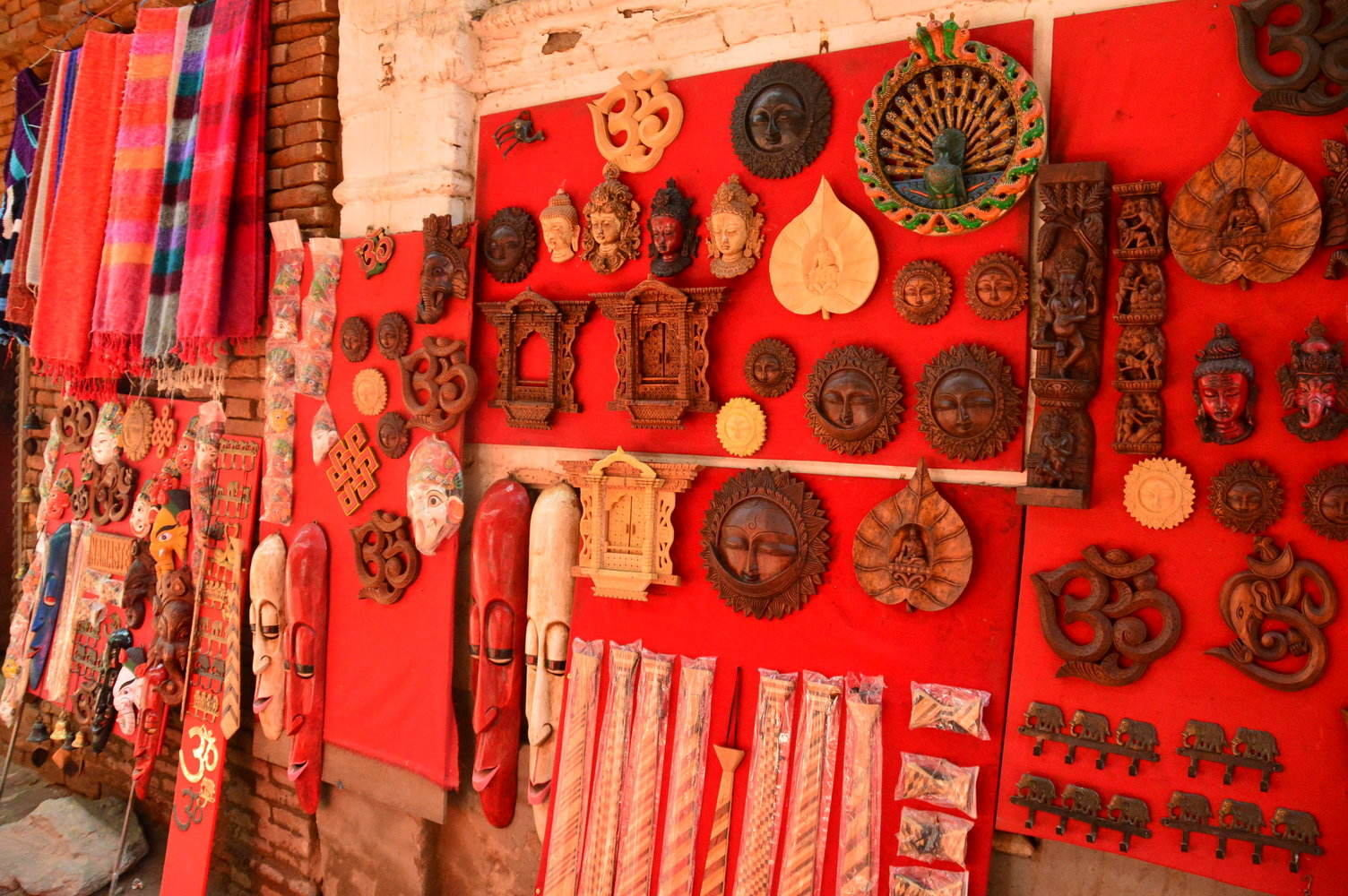 wooden handicrafts on red cloths up on a wall in bhaktapur