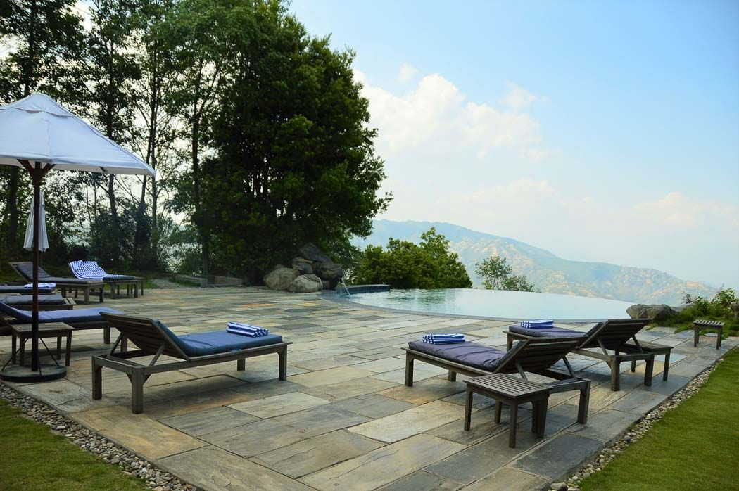 infinity pool and sun loungers at Dwarika's Dhulikhel resort