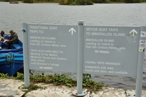 signs with boat trip options for the lake in front of ross castle killarney ireland