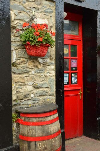 red door with black frame red hanging basked and red barrel killarney ireland