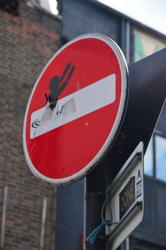 stop sign with small black person stickered on east london