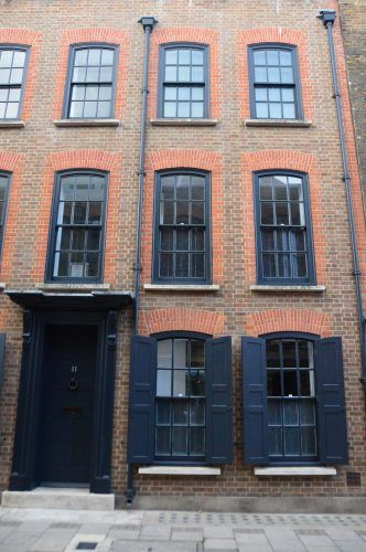 classic brick building with navy blue shutters and window treatments east london