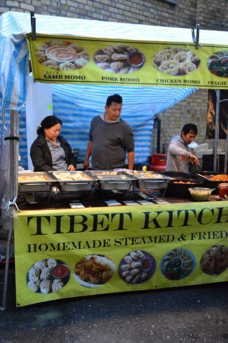 people serving food at tibet kitchen stand east london