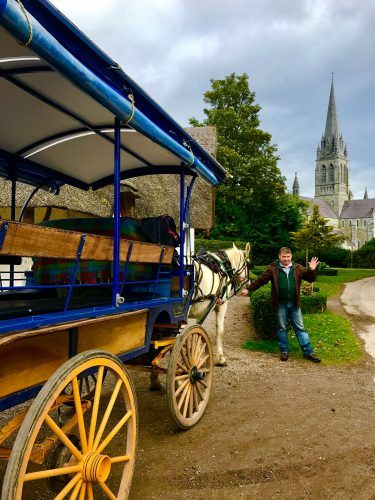 jaunting cart with friendly driver and church in background killarney ireland