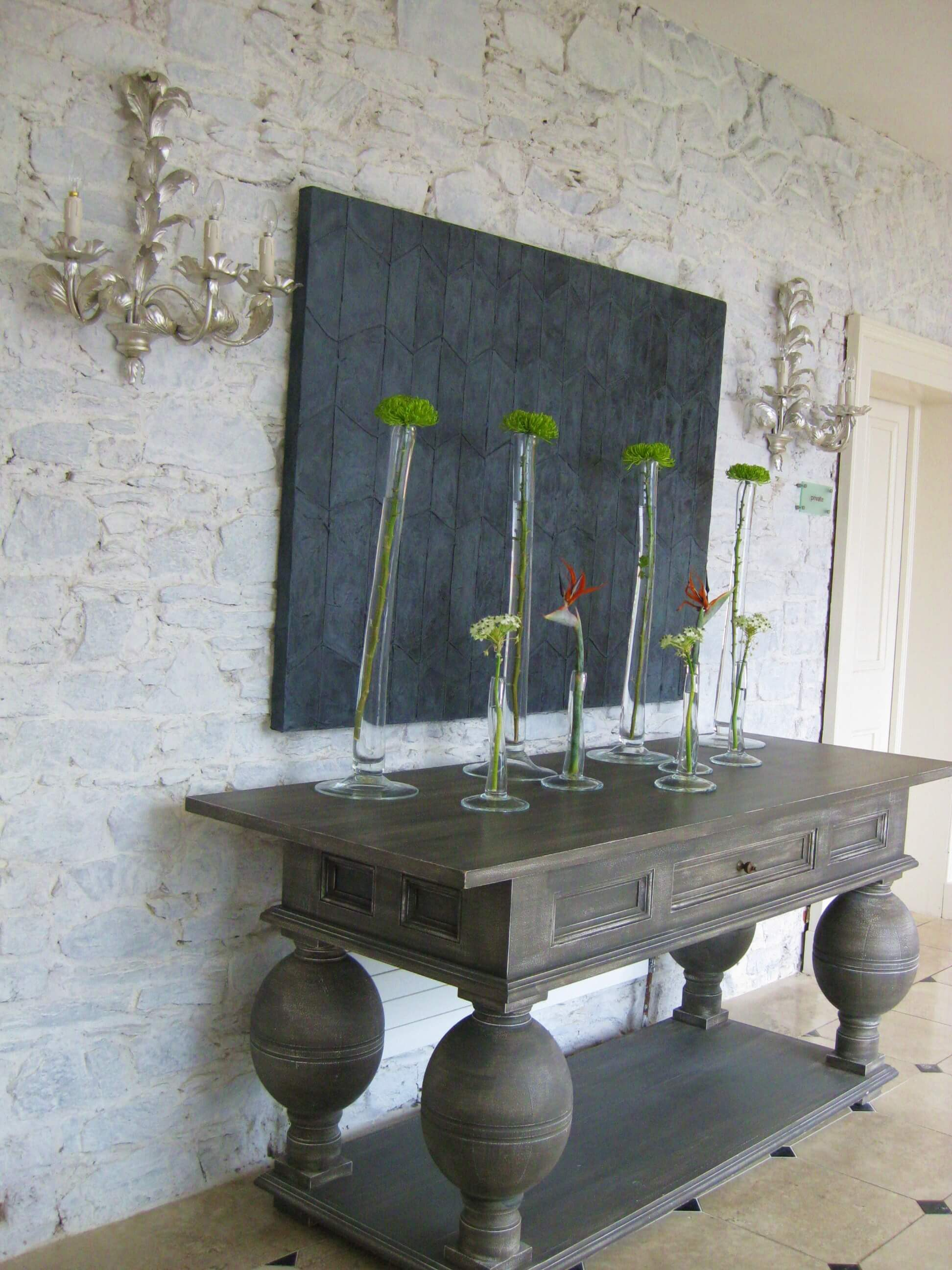 wooden side board with tall vases and flowers monart spa ireland