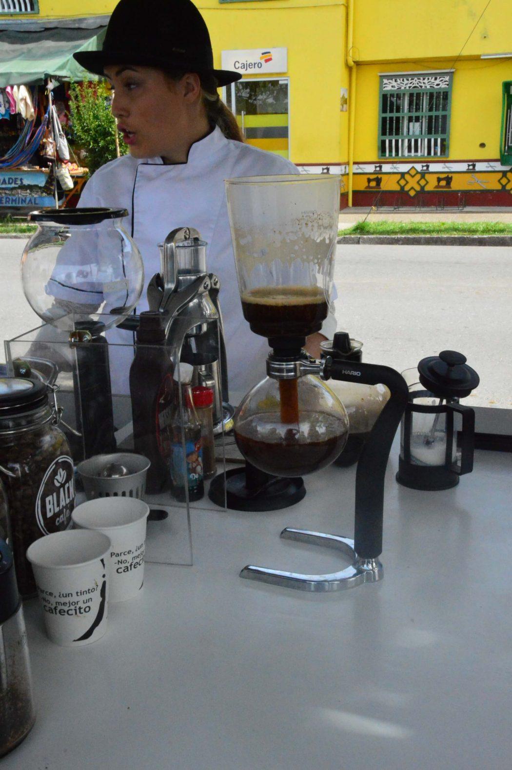 woman prepares coffee in gutape on street