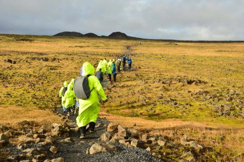 People in raincoats trekking across a lava field towards a volcano ICeland