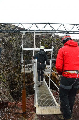 person crossing a steel path to a steel lift on the inside the volcano iceland tour