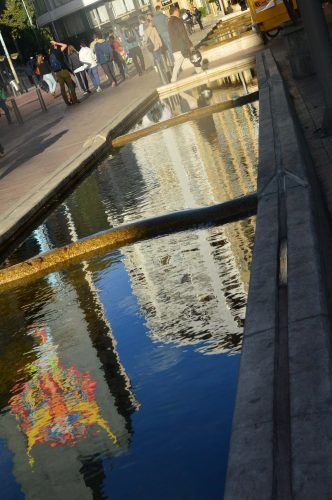 White building and street art reflected in water bogota