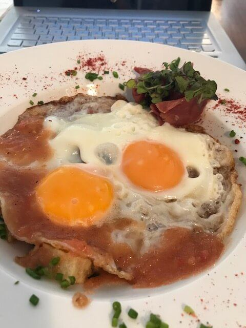 baked eggs with tomato on a white plate at Ganso and Castor Medellin