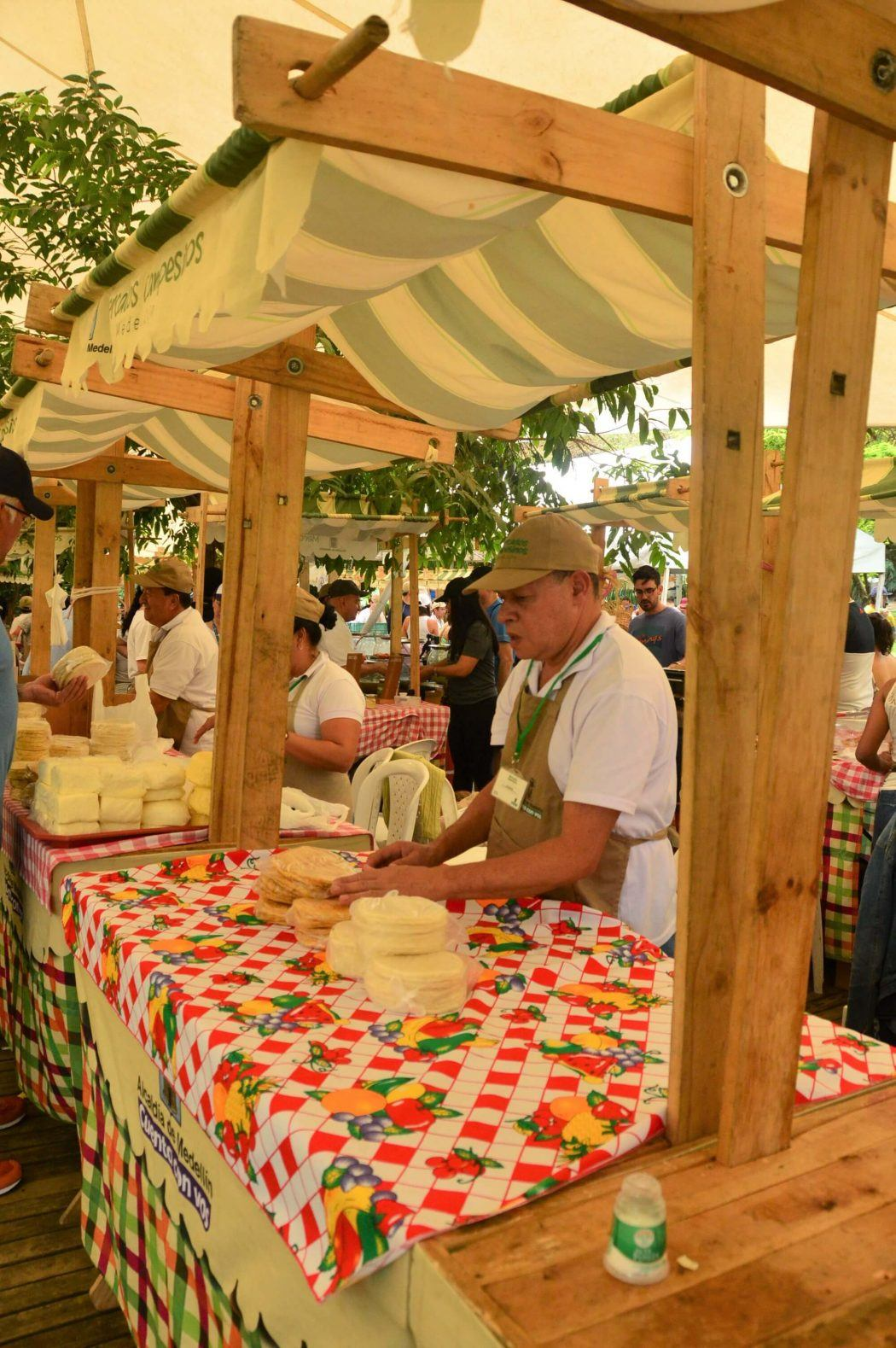 man with cheeses at el poblado farmers market