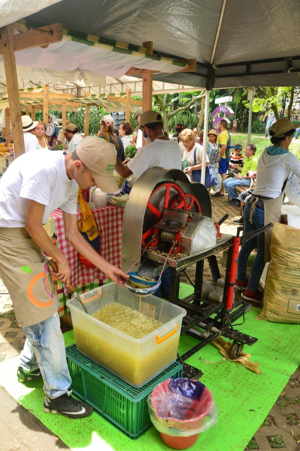 man making juice at el poblado farmers market medellin