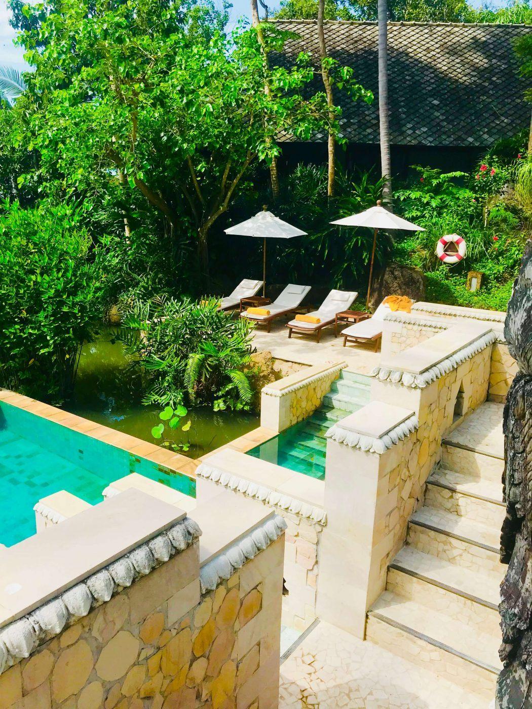 kamalaya pool with lounge chairs and umbrellas