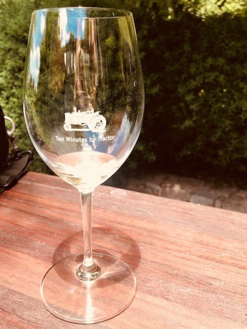 wine glass with ten minutes by tractor logo outside on a wooden table