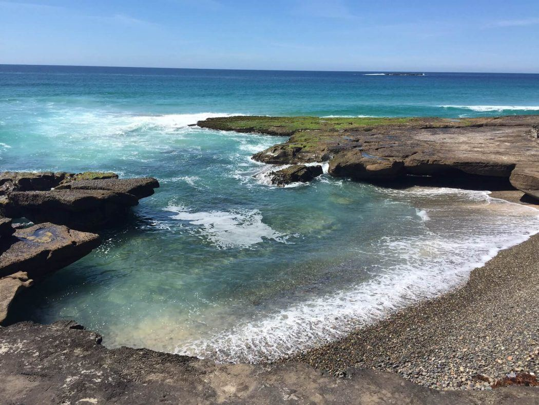 ocean water against rocks with moss on the australia east coastline