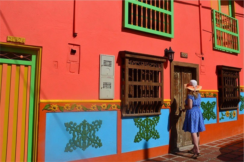woman in colourful dress outside colourful building in Guatape