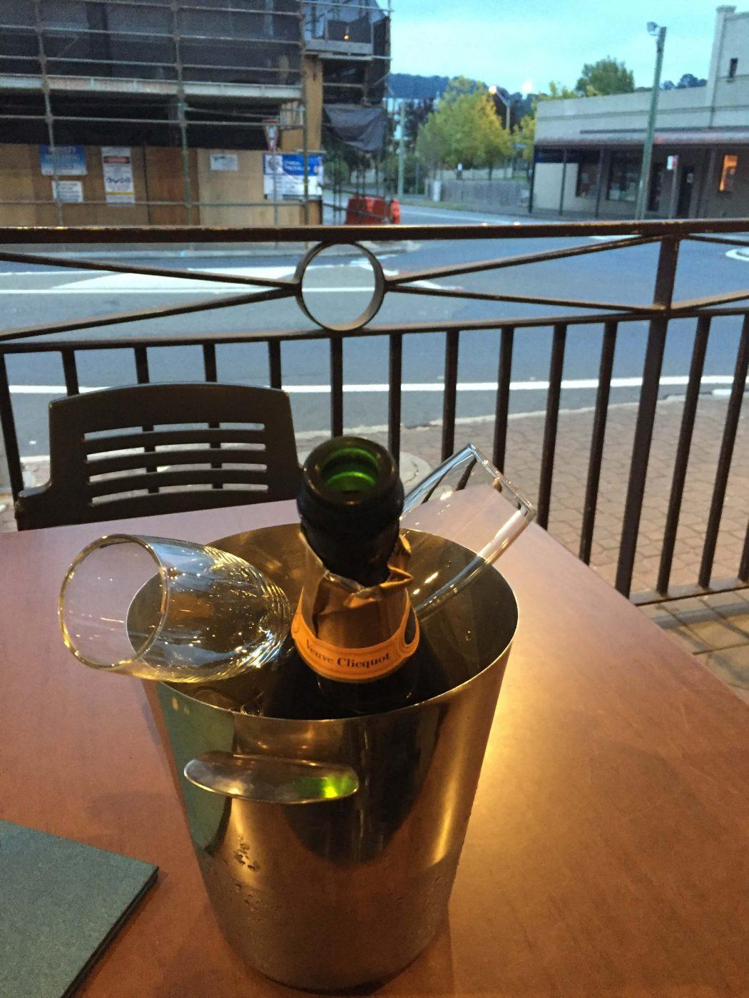 bottle of veuve clicquot in an ice bucket on an outside table at the bowral hotel