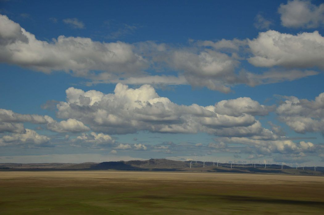 long distance view of wind farms with big sky and clouds in australia