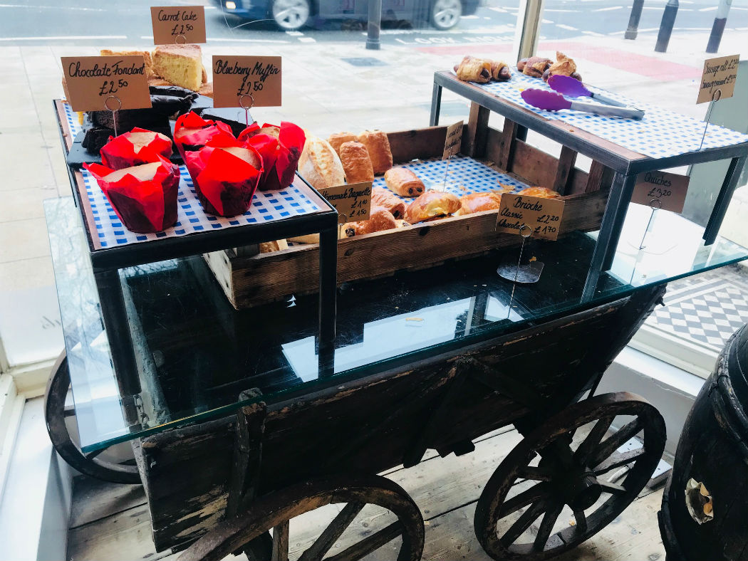 cakes on a wheelbarrow display in a clapham coffee shop