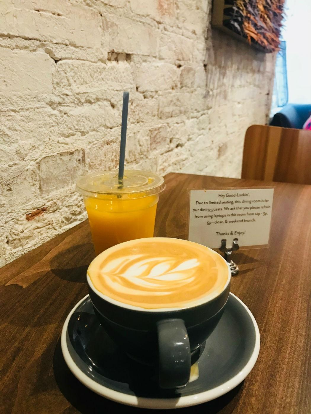 cup of coffee with orange juice on a wooden cafe table