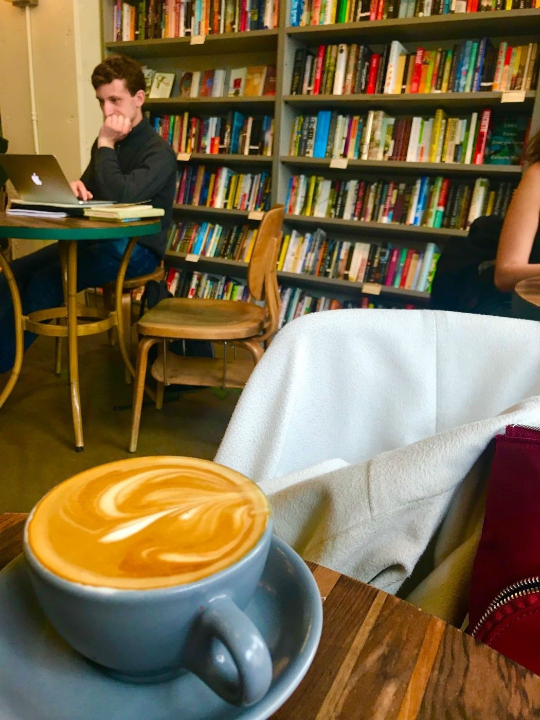 Cup of coffee with bookshelf behind and person at Bird in Hand Cafe Baltimore